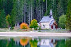 Poca cappella nel lago Braies in montagne delle dolomia Immagine Stock Libera da Diritti