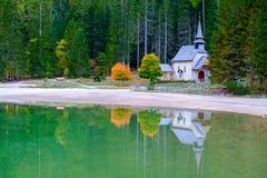 Poca cappella nel lago Braies in montagne delle dolomia Fotografia Stock Libera da Diritti