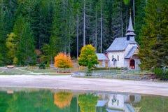 Poca cappella nel lago Braies in montagne delle dolomia Immagini Stock Libere da Diritti