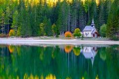 Poca cappella nel lago Braies in montagne delle dolomia Fotografia Stock