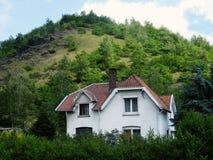 Poca casa bianca vicino alle montagne Immagini Stock