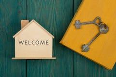 Poca casa con el texto y x22; Welcome& x22; , libro y llave Fotografía de archivo libre de regalías