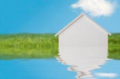Poca casa de madera blanca que se hunde en el agua Imágenes de archivo libres de regalías