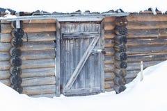 Poca casa de madera cubierta con nieve y rodeada con la naturaleza del invierno imagenes de archivo