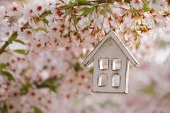 Poca casa de madera en primavera con la cereza del flor Imagenes de archivo