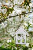 Poca casa di legno in primavera con la ciliegia del fiore Fotografie Stock Libere da Diritti