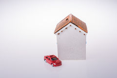 Poca casa di modello e un'automobile rossa di modello Fotografie Stock Libere da Diritti