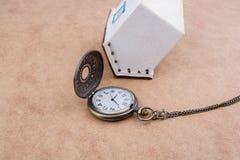 Poca casa di modello e un orologio da tasca Immagini Stock