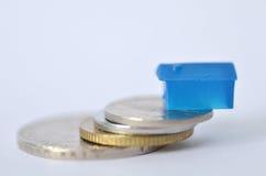 Poca casa di plastica sulle monete del metallo Fotografia Stock
