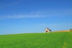Poca casa nel campo di erba immagini stock libere da diritti