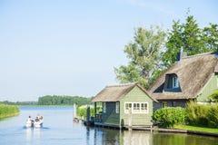 Poca casa que permanece en el río y los visitantes en Giethoorn Imágenes de archivo libres de regalías