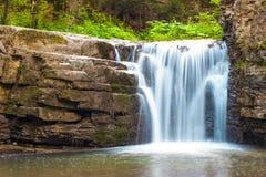 Poca cascada en bosque de la montaña con agua que hace espuma sedosa foto de archivo libre de regalías