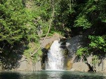Poca cascata sfocia nel lago blu, Grenoble fotografia stock