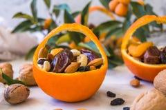 Poca cesta hizo de la naranja fresca llenada de las frutas secas; almendras, fechas, pasas y nueces fotos de archivo