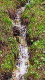 Poca corriente del agua que fluye abajo de la montaña Foto de archivo