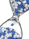 Época de la medicina Píldoras en reloj de arena Fotos de archivo libres de regalías