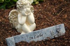 Poca escultura del ángel adorna en pequeño jardín con las flores en frente lo y una muestra - en alemán del intercambio de halago Fotografía de archivo libre de regalías