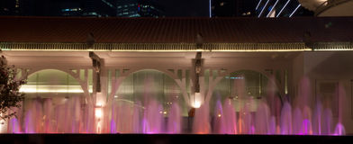 Poca fuente de agua Singapur en la noche delante del edificio colonial Foto de archivo libre de regalías