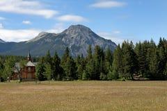 Poca iglesia de madera roja contra bosque imagenes de archivo