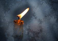 Poca llama de vela detrás del vidrio de la ventana congelado Imagen de archivo libre de regalías