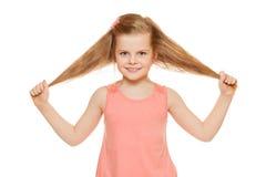 Poca muchacha alegre de la diversión en una camisa rosada sostiene el pelo de las manos, aislado en el fondo blanco Imagen de archivo