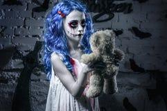 Poca muchacha azul del pelo en vestido sangriento con el maquillaje asustadizo de Halloween con el oso de peluche Imagen de archivo libre de regalías