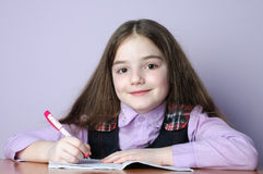 Poca muchacha de la escuela que hace homeworks en el escritorio Imagen de archivo libre de regalías