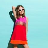 Poca muchacha de la moda que presenta en la luz del sol Fotografía de archivo