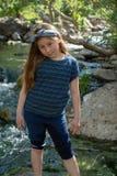 Poca muchacha de Latina que sonríe tímidamente y que mira abajo mientras que se coloca delante de una corriente y del bosque en l imagenes de archivo