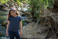Poca muchacha de Latina que sonr?e t?midamente y que mira abajo mientras que se coloca delante de una corriente y del bosque en l foto de archivo libre de regalías