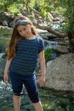 Poca muchacha de Latina que sonr?e t?midamente y que mira abajo mientras que se coloca delante de una corriente y del bosque en l imagen de archivo libre de regalías