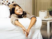 Poca muchacha morena linda en casa u cercano sonriente feliz interior Imagen de archivo libre de regalías