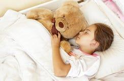 Poca muchacha morena que duerme en cama con el oso de peluche Imagenes de archivo