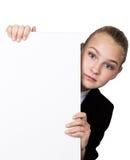 Poca mujer de negocios que se coloca detrás y que se inclina en una cartelera o un cartel en blanco blanca, expresa diferente Fotos de archivo libres de regalías