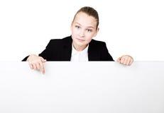 Poca mujer de negocios que se coloca detrás y que se inclina en una cartelera o un cartel en blanco blanca, expresa diferente mue Fotografía de archivo