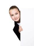Poca mujer de negocios que se coloca detrás y que se inclina en una cartelera o un cartel en blanco blanca, expresa diferente Fotografía de archivo libre de regalías