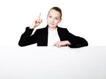 Poca mujer de negocios que se coloca detrás y que se inclina en una cartelera o un cartel en blanco blanca, expresa diferente índ Imágenes de archivo libres de regalías