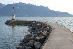 Poca nave faro all'estremità di un molo roccioso Fotografia Stock