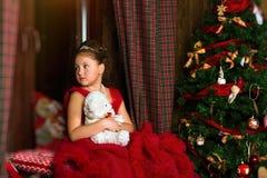 Poca princesa de la Navidad, muchacha mira hacia fuera la ventana Imagenes de archivo
