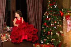Poca princesa de la Navidad, muchacha mira hacia fuera la ventana Imágenes de archivo libres de regalías