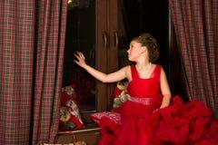 Poca princesa de la Navidad, muchacha mira hacia fuera la ventana Foto de archivo libre de regalías