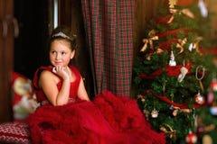 Poca princesa de la Navidad, muchacha mira hacia fuera la ventana Foto de archivo