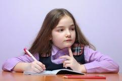 Poca ragazza del banco che fa i homeworks allo scrittorio Fotografie Stock Libere da Diritti