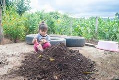 Poca ragazza dell'Asia è seminante o pianta una pianta Fotografia Stock