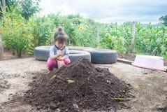 Poca ragazza dell'Asia è seminante o pianta una pianta su un naturale, Fotografie Stock