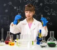 Poca ragazza dello smarl nel laboratorio di chimica che fa un esperimento Fotografie Stock