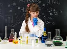 Poca ragazza dello smarl nel laboratorio di chimica che fa un esperimento Fotografia Stock Libera da Diritti