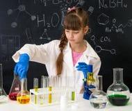 Poca ragazza dello smarl nel laboratorio di chimica che fa un esperimento Fotografie Stock Libere da Diritti