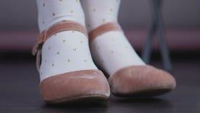 Poca ragazza di irrequietezza in scarpe sveglie che batte i piedi allegro le sue gambe che attende i genitori archivi video