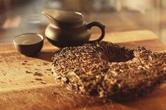 Poca teiera con il mattone del tè sulla tavola alla luce solare fotografie stock